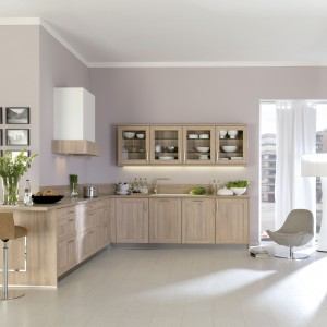 Piękna, delikatnie klasycyzująca kuchnia z frontami zdobionymi prostym rysunkiem i przeszklonym rzędem szafek górnych. Do wzornictwa, nawiązującego do tradycyjnej stylistyki idealnie pasowały ciepłe kolory drewna. Fot. Brigitte Kuechen.