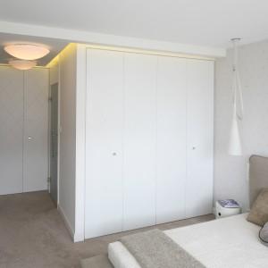 W sypialni wygospodarowano miejsce na dość pojemną szafę. Białe fronty skrywają liczne szafki i półki, jak również optycznie powiększają wnętrz. Biel doskonale pasuję również do spokojnej, stonowanej aranżacji. Projekt: Katarzyna Dudko, Michał Dudko. Fot. Bartosz Jarosz.