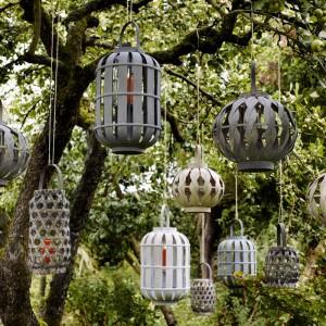 Dekoracyjne lampiony zawieszone na drzewie mogą stać się ciekawą dekoracją ogrodu zarówno dzień, jak i w nocy. Lampiony widoczne na zdjęciu oferuje marka Broste Copenhagen. Fot. Broste Copenhagen.