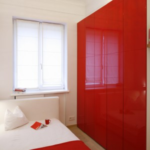 Czerwone, lakierowane drzwi szafy, zajmujące prawie cała powierzchnię ściany spektakularnie odmieniły charakter niewielkiej, białej sypialni. Dzięki nim wnętrze zyskało wyrazisty charakter. Projekt: Agnieszka Żyła. Fot. Bartosz Jarosz.