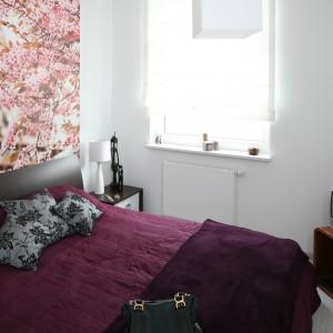 Największa dekoracją niewielkiej, białej sypialni jest efektowna fototapeta z motywem kwitnącej wiśni, która nadaje wnętrzu romantyczny charakter. Projekt: Anna Maria Sokołowska. Fot. Bartosz Jarosz.