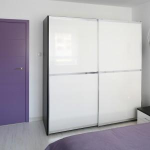 Designerski wygląd wnętrza to bez wątpienia zasługa oryginalnych, fioletowych drzwi. Efekt wzmacnia narzuta w tej samej barwie. Projekt: Joanna Ochota. Fot. Bartosz Jarosz.