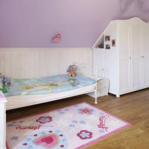 W przestrzeni pod skosami ustawiono piękne, kute łóżko oraz drewniany stolik nocny i szafę na ubrania, która idealnie wpasowuje się w trudną przestrzeń. Fot. Bartosz Jarosz.