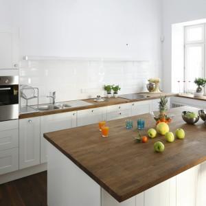 Białą kuchnię ocieplają drewniane blaty, w tym jeden bardzo obszerny, przedłużony tak, aby można było przy nim swobodnie ustawić kilka krzeseł i zjeść posiłek. Projekt: Konrad Grodziński. Fot. Bartosz Jarosz.