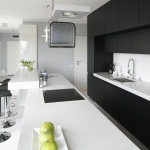 Na długim blacie zmieszczono również strefę gotowania i sporą powierzchnie roboczą, przy której w pełni wygody można przyrządzać posiłki, serwowane na nałożonym na wyspę, wyższym blacie. Projekt: Maciejka Peszyńska-Drews. Fot. Bartosz Jarosz.