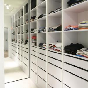 Ważną częścią sypialnego wnętrza jest garderoba, wyposażona w obszerny regał z szufladami oraz otwarta szafę. Fot. Bartosz Jarosz.