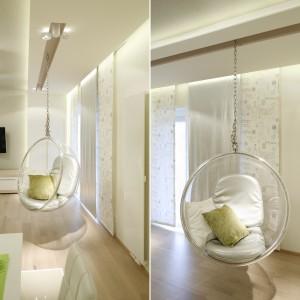 Najciekawszym elementem aranżacji salonu jest huśtawka, która pełni funkcję dekoracyjną i praktyczną. Zawieszono ją na specjalnych krokwiach, dzięki czemu jest wygodna i bezpieczna w użytkowaniu. Projekt: Marta Kilan. Fot. Bartosz Jarosz.