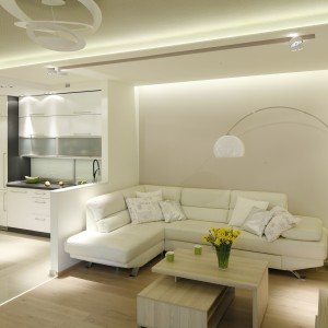 """Priorytetem przy aranżacji mieszkania było oświetlenie, które w połączeniu z jasną kolorystyką mebli i ścian dało efekt rozświetlonego wnętrza. Światło delikatnie wydobywa się z """"obniżeń"""" w suficie, rozświetlając zarówno część salonu, jak i kuchni. Projekt: Marta Kilan. Fot. Bartosz Jarosz."""