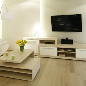 Asymetryczne meble w salonie i brak dywanu nadają pomieszczeniu nowoczesny charakter. Projekt: Marta Kilan. Fot. Bartosz Jarosz.