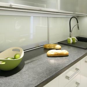 Blat w kuchni zdobi piękny wzór Arabeska Czarna. Ścianę nad nim pokrywa szkło, harmonizujące z przeszkleniami górnych szafek. Projekt: Marta Kilan. Fot. Bartosz Jarosz.