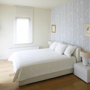 Subtelna tapeta w kolorze błękitu, zdobiąca ścianę za łóżkiem to najciemniejszy element aranżacji sypialni, urządzonej z wykorzystaniem białych mebli. Dekorację w chłodnej tonacji równoważy podłoga z jasnych desek, która subtelnie ociepla wnętrze. Projekt: Małgorzata Borzyszkowska. Fot. Bartosz Jarosz.