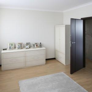 Wyposażenie sypialni uzupełniają elegancka komoda, na której ustawiono wystawę zdjęć oraz szafa, w tej samej stylistyce co łóżko. Projekt: APT Białystok. Fot. Bartosz Jarosz.