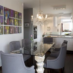 """W jadalni połączonej z kuchnią na uwagę zasługuje szklany blat wsparty na wyrzeźbionych w drewnie nogach. To unikatowy mebel. Surowość i ascezę stołu łagodzi komplet sześciu wytwornych i eleganckich berżerek w kolorze delikatnego """"zszarzałego"""" fioletu. Całość wieńczy żyrandol (Maria Teresa) wykonany ze szkła akrylowego. Projekt: Małgorzata Szajbel-Żukowska, Maria Żychniewicz. Fot. Marcin Onufryjuk."""