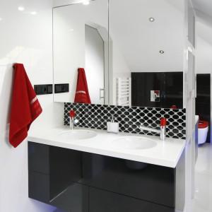 Elementy w czerwonym kolorze pięknie ożywiają wnętrze łazienki. Duże lustra nie tylko optycznie powiększają przestrzeń. Skrywają również pojemne szafki. Projekt: Marta Kilan. Fot. Bartosz Jarosz.