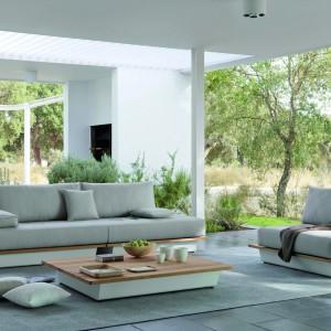 Sofa marki Manutti łączy ekologiczne tkaniny w modnych szarościach z ponadczasowym drewnem iroko. Fot.  Manutti.