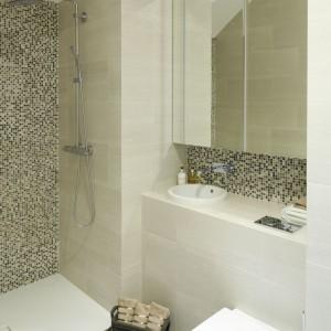 Niewielka łazienka została urządzona niezwykle szykownie dzięki piaskowym płytkom na ścianach, beżowo-brązowej mozaice oraz płytkom podłogowym przypominającym kamień. Projekt: współpraca Tomasz Żemojcin, Ventis, Ventana. Fot. Bartosz Jarosz.