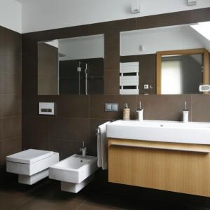 Ciemnobrązowe podłużne płytki, którymi wyłożono ściany i podłogę sprawiają, że łazienka jest niezwykle przytulna i elegancka. Dla kontrastu dobrano szafkę podumywalkową w kolorze jasnego drewna. Projekt: Michał Mikołajczak. Fot. Bartosz Jarosz.
