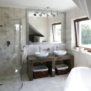 Przestronna doświetlona łazienka niezwykle elegancko prezentuje się w beżach. Ściany i podłogę wyłożono marmurem, a strefę prysznica marmurową mozaiką. Brązowe detale dopełniają całość. Projekt: Beata Ignasiak. Fot. Bartosz Jarosz.