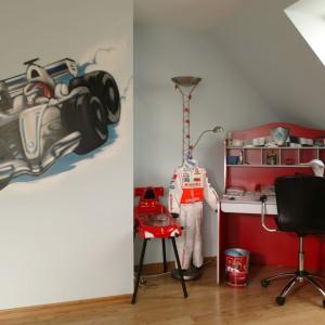 W najjaśniejszym miejscu pokoju, czyli pod oknem dachowym, ustawiono czerwone biurko wraz z krzesłem obrotowym, tworząc strefę przeznaczoną do nauki. Fot. Bartosz Jarosz.