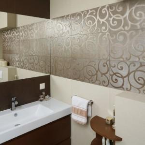 W łazience lekki styl glamour został osiągnięty dzięki metalicznym dekorom na ścianach. Wyglądają one niezwykle elegancko w towarzystwie beżowych i brązowych płytek. Całość dopełniają fornirowane ciemnym drewnem meble. Projekt: Kinga Śliwa. Fot. Bartosz Jarosz.