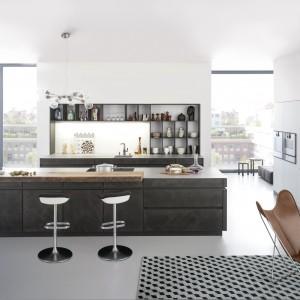 Wyspa w kuchni zaadaptowana na niewielki dwuosobowy bar. Wolną część blatu wykorzystano na urządzenie powierzchni roboczej, a powierzchnie do serwowania jedzenia bądź drinków stanowi nakładany, delikatnie wysunięty blat. Fot. Leicht, model Concrete.