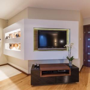 Telewizor wkomponowano w zabudowę z płyt g-k, w której po drugiej stronie wyżłobiono efektownie podświetlone półki. Służą one za galerię domowych dekoracji. Projekt i zdjęcia: Gabinet Wnętrz.