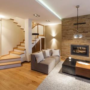 Klatkę schodową otwarto na salon. Betonowe schody, pomalowane na biało, z drewnianymi stopniami stanowią pełnoprawny element dekoracyjny wnętrza. Projekt i zdjęcia: Gabinet Wnętrz.