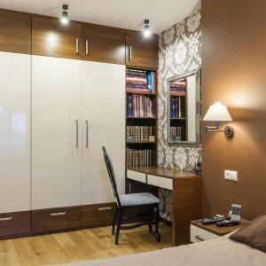 Jedną ze ścian w sypialni pani i pana domu pokryto w całości praktyczną zabudową, poprowadzoną od podłogi, aż po sam sufit. Niewielki fragment wykorzystano jako biblioteczkę, resztę adaptując na praktyczną garderobę. Projekt i zdjęcia: Gabinet Wnętrz.