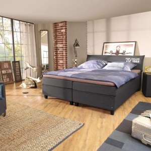Zestaw do sypialni Jute marki Tom Tailor tworzy łóżko, stoliki nocne w formie kubików oraz fotel. Wszystkie elementy zestawu wykończone są tkaniną w eleganckim, grafitowym kolorze. Fot. Tom Tailor.
