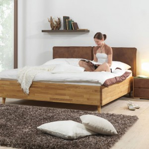Nowoczesny zestaw z serii Premium marki Ada w urzekający sposób łączy w sobie solidność dębu z subtelnością zamszu, którym wykończono zagłówek łóżka oraz fronty szafek nocnych. Fot. Ada.