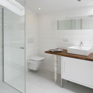 Niski brodzik ze szklaną kabiną prysznicową stanowią kontrast dla lekko stylizowanej strefy umywalkowej i nadają łazience nowoczesny charakter. Projekt: Konrad Grodziński. Fot. Bartosz Jarosz.