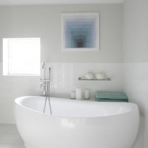 W łazience jednak zdecydowanie dominuje biel. Wnętrze urządzono z myślą o wygodzie i funkcjonalności. Pomimo minimalistycznej stylistyki jest niezwykle eleganckie. Projekt: dom pokazowy na osiedlu Ventana. Fot. Bartosz Jarosz.