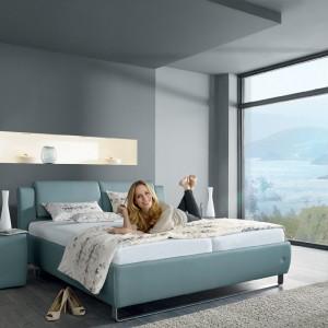 Nowoczesne łóżko marki Ruf Betten o wymiarach 180x200 cm wykończone skórą ekologiczną w uspokajającym, błękitnym kolorze. Ciekawy design sprawia, że mebel jest zarazem praktyczną dekoracją sypialni. Fot. Studio Asymetria.