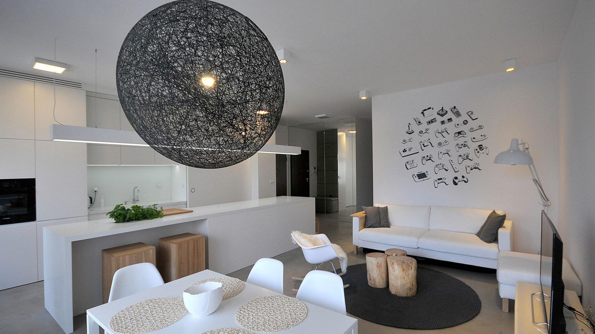 Jasną przestrzeń dodatkowo rozświetla punktowe oświetlenie przy suficie oraz lampa Moooi Random nad stołem, która jest tu głównym elementem wystroju, czarnym słońcem białego wnętrza. Projekt: TK Architekci. Fot. Wojciech Szwej, Jose Teixeira.
