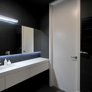 Oprócz czerni to lustra grają w łazience główną rolę - jedna ze ścian została pokryta nimi w całości. Projekt: TK Architekci. Fot. Wojciech Szwej, Jose Teixeira.