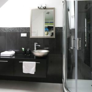 Przy pomocy czarnych płytek wykończonych pasem mozaiki zaznaczono w tej łazience poszczególne strefy użytkowe - prysznica, umywalki i toalety. Na jednolitą aranżację składają się również czarne meble łazienkowe. Projekt: Katarzyna Merta-Korzniakow. Fot. Bartosz Jarosz.