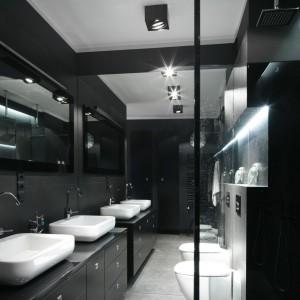 Ta czarna łazienka zyskała niezwykłą głębię dzięki jednej ze ścian w całości pokrytej lustrem. Ciemna kolorystyka świetnie eksponuje białą ceramikę sanitarną. Wnętrze jest nowoczesne i eleganckie. Projekt: Maciejka Peszyńska-Drews. Fot. Bartosz Jarosz.