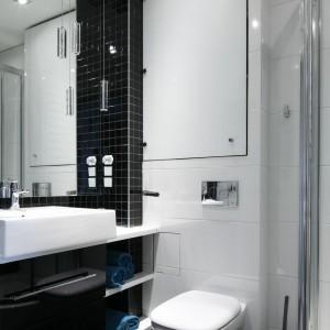 Kolejna łazienka, w której czerń wykorzystano, by podkreślić strefy użytkowe. Biały blat pod umywalką i półki przerywają czarną, jednorodną aranżację. Projekt: Marta Kilan. Fot. Bartosz Jarosz.