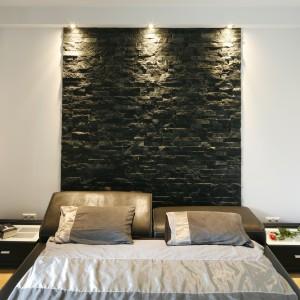 Ściana wyłożona łupkiem naturalnym harmonizuje z nowoczesnym łóżkiem tapicerowanym skórą. Z uwagi na to, że dekoracja jest szerokości mebla, wygląda jak wysoki zagłówek. Projekt: Michał Wielecki, Łukasz Hoffman. Fot. Bartosz Jarosz.