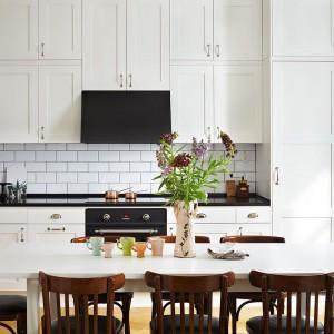 Białe meble kuchenne w delikatnie klasycznym stylu wspaniale wyglądają jeśli połączymy je z tradycyjnymi białymi kaflami lub z płytkami imitującymi takie kafle. Z białą ścianą nad blatem estetycznie będzie kontrastować czarny blat kuchenny. Fot. Ballingslov.