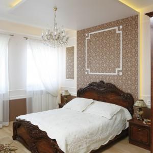 Chociaż sypialnia urządzona jest w stylu klasycznym, zastosowano w niej nowoczesne rozwiązanie w postaci sufitu podwieszanego. Konstrukcja ta dodatkowo eksponuje piękny, złocony żyrandol. Projekt: Magdalena Mirek- Roszkowska. Fot. Bartosz Jarosz.