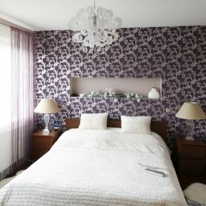 Dekoracyjna lampa sufitowa przypominająca formą kwiat harmonizuje z największą dekoracją sypialni - tapetą na ścianie za łóżkiem. Ponadto roślinne motywy wprowadzają do wnętrza romantyczny styl. Projekt: Piotr Stanisz. Fot. Bartosz Jarosz.