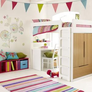 Białe łóżko na antresoli to miejsce nie tylko do spania, ale zabawy oraz nauki. Ciekawa aplikacja na ścianie, dekoracyjne chorągiewki czy kolorowy dywan sprawiają, że wnętrze jest nie tylko praktyczne ale i wesołe. Fot. Aspace.