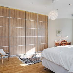 Obszerna zabudowa na całą ścianę z drzwiami w kolorze lakierowanego drewna pięknie ociepla ociepla sypialnię urządzoną w bieli. Przytulności dodaje krzesło z drewnianej konstrukcji oraz niewielka konsola. Fot. Alvhem Makleri.