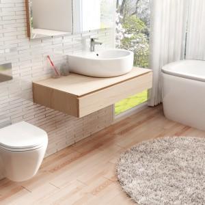 W łazience inspirowanej przyrodą należy dobierać minimalistyczne sprzęty, które nie zaburzą harmonijnej aranżacji. Drewno pięknie podkreśli opływowe, miękkie kształty poszczególnych elementów wyposażenia łazienki. Na zdjęciu: kolekcja Peonia. Fot. Deante.