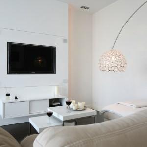 W niewielkich rozmiarów salonie telewizor zamontowano naprzeciwko wygodnej sofy. Zamontowany w ciągnącym się na całą wysokość pomieszczenia panelu lakierowanym na biało, prezentuje się naprawdę efektownie. Projekt: Agnieszka Żyła. Fot. Bartosz Jarosz.