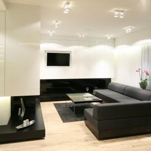 W biało-czarnym salonie telewizor zamontowano na tle lakierowanych na wysoki połysk białych szafek montowanych pod sufit. Projekt: Dominik Respondek. Fot. Bartosz Jarosz.