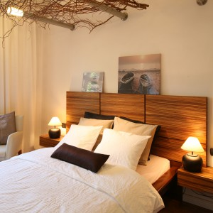 Zagłówek łóżka eksponujący piękny rysunek drewna wnosi do beżowej sypialni naturalny urok. Efekt wzmacnia oryginalna dekoracja sufitu wykonana z suchych gałęzi. Projekt: Urszula i Jakub Górscy. Fot. Bartosz Jarosz.