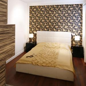 Fornir oraz wzorzysta tapeta w ciepłych kolorach na ścianie za łóżkiem, korespondują z drewnianą podłogą. Dzięki temu sypialnia jest przytulna i harmonijna wizualnie. Projekt: Agnieszka Żyła. Fot. Bartosz Jarosz.