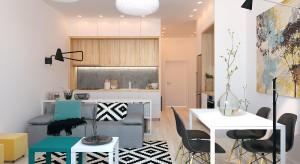 Jasne mieszkanie, w którym dominuje kolor biały. Charakter całego wnętrza podkreślają kolorowe dodatki w postaci między innymi lamp i krzeseł.
